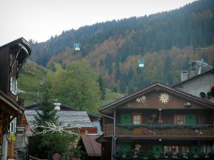 La Clusaz - Chalets of the village (winter and summer sports resort), cable car (ski lift) and forest in autumn
