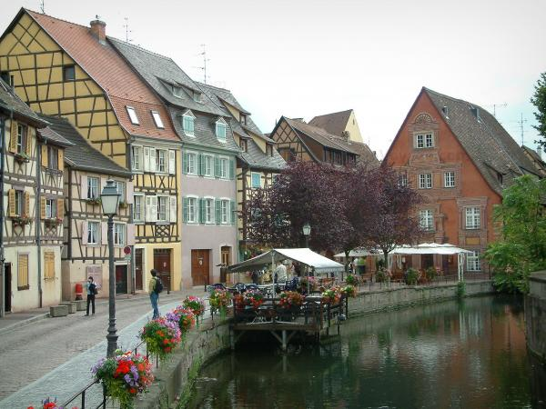 Colmar - Petite Venise (Little Venice): Lauch river, Poissonnerie quayside decorated with flowers, café terrace, trees and colourful half-timbered houses