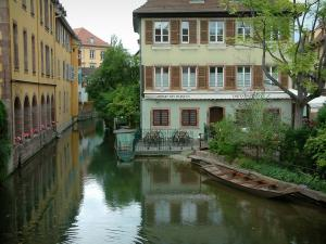 Colmar - Petite Venise (Little Venice): Lauch river with a boat, trees, café terrace and colourful houses