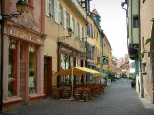 Colmar - Marchands street and its houses with in colourful facades and a café terrace
