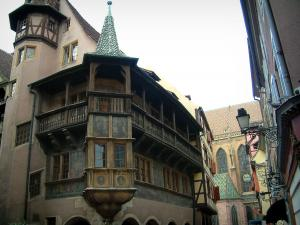Colmar - Pfister house with its painted facade, its oriel angle window with two floors and its wooden gallery, the Saint-Martin collegiate church in background