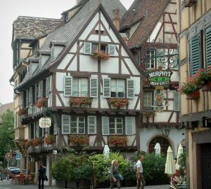 Colmar - Timber-framed houses with geranium flowers and forged iron shop signs