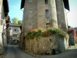 Conflans medieval town - Sloping narrow street with the Ramus tower decorated with flowers, houses and fountain of the village