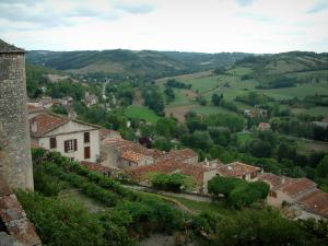 Cordes-sur-Ciel - View of gardens, roofs of the houses in the city and surrounding hills