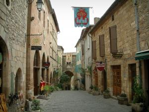 Cordes-sur-Ciel - Paved street in the upper town (medieval town) with its stone houses and facades decorated with forged iron shop signs, its workshops (shops), its flowers and its plants