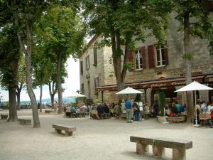 Cordes-sur-Ciel - The Bride square with its stone benches, its trees, its restaurant terrace, its stone houses and its view of the surrounding hills