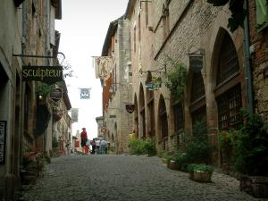 Cordes-sur-Ciel - Paved sloping street lined with flowers and plants, stone houses with facades decorated with forged iron shop signs and flags, workshops and art galleries