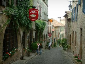 Cordes-sur-Ciel - Paved sloping narrow street, the Grand Écuyer (Rider) house home to a hotel and a restaurant, stone houses of the medieval town