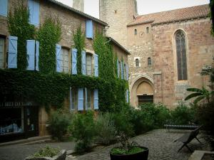 Cordes-sur-Ciel - Square decorated with benches and shrubs, stone house covered with ivy and with blue shutters, Saint-Michel church