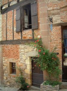 Cordes-sur-Ciel - Pink climbing roses and facade of a house in the medieval town mixing brick, stone and wood