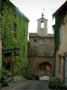 Cordes-sur-Ciel - Narrow paved street, houses covered with ivy and the Horloge gateway