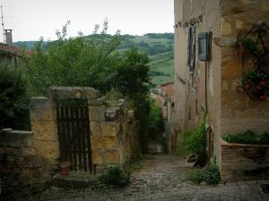 Cordes-sur-Ciel - Wicket of a garden and houses in the medieval town with view of the surrounding hills