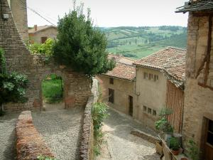 Cordes-sur-Ciel - Narrow paved streets and houses of the medieval town with view of the surroundings