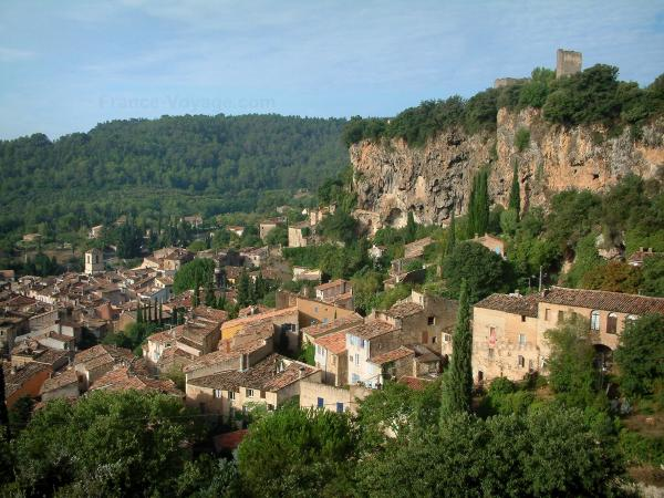 Cotignac - View of the ruins of the castle (two towers) situated at the top of the tuff cliff pierced by caves, houses of the village, trees and forest