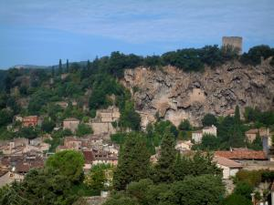 Cotignac - Trees, houses of the village, ruins of the castle (tower) and the tuff cliff pierced by caves