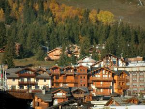 Courchevel - Spruces and trees in autumn, chairlift (ski lift), chalets and residences of the Courchevel 1850 ski resort (winter sports)