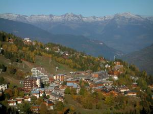 Courchevel - Ski resort (winter sports) with chalets, residences, ski lifts of the ski area, spruces, trees in autumn and mountains