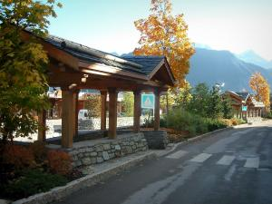 Courchevel - Street of the ski resort (winter sports) with a wooden shelter, shrubs and trees in autumn