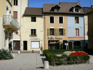 Crémieu - Medieval town: facades of houses, shops and flowerbed