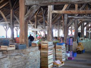 Crémieu - Under the medieval covered market hall: oak roof structure and crates on the market