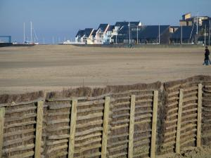 Deauville - Côte Fleurie (Flower coast): fence in foreground, beach and marina residences in Port-Deauville