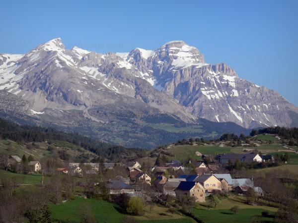 Dévoluy mountain range - Houses of a village, prairies, trees and mountains with snowy tops (snow)