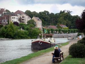 Dole - Rhone to Rhine canal with moored barges, banks decorated with a bench, building, houses of the city and trees