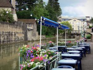 Dole - Café terrace along the water, rail decorated with flowers, Tanneurs canal, houses and buildings of the city