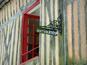 Domfront - Detail of a half-timbered house facade with red window and forged iron sign