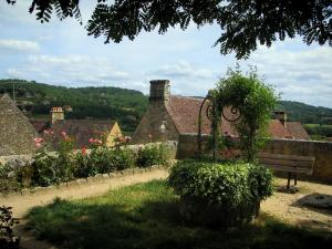 Domme - Garden (well, bench and rosebushes) with view of the roofs of the fortified town, in the Dordogne valley, in Périgord