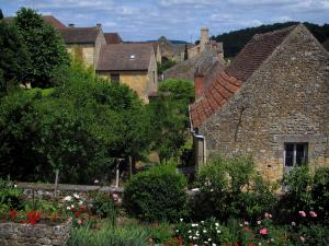 Domme - Flowers in foreground and houses of the fortified town, in the Dordogne valley, in Périgord