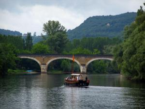 Dordogne valley - Navigating gabarre, bridge spanning the River Dordogne, trees along the water, forest and hill, in Périgord