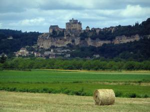 Dordogne valley - Straw bale in foreground and fields with view of the village of Beynac-et-Cazenac, its castle, its cliff and its houses, cloudy sky, in Périgord