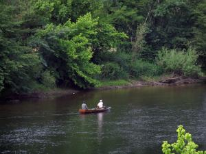 Dordogne valley - The River Dordogne, fishermen on a boat and trees along the water, in Périgord