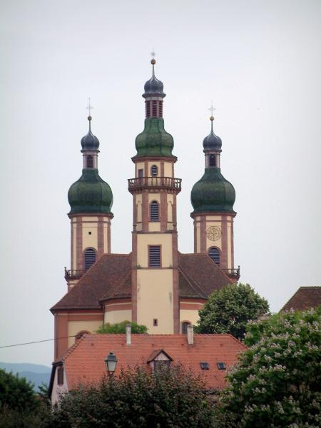 Ebersmunster - Abbey church with three bulb bell towers, roof of a house and trees
