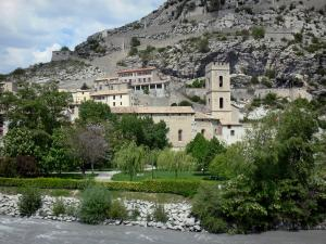 Entrevaux - Church with crenellations of the Notre-Dame-de-l'Assomption cathedral, wooded park alongside the Var river, houses of the medieval village and winding fortified ramp leading to the citadel (fortifications)