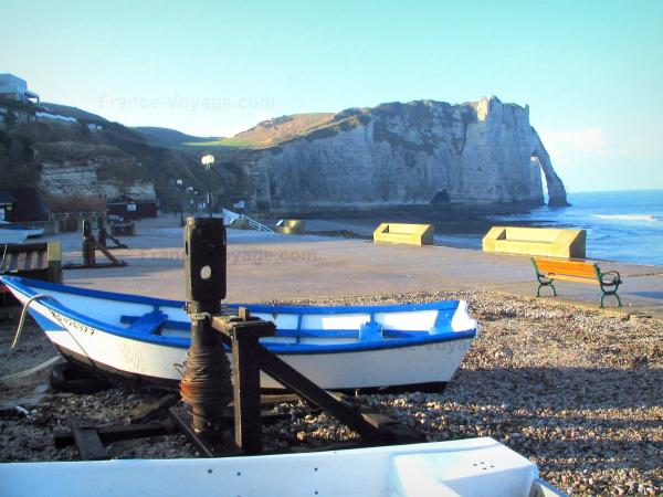 Étretat - Boats, pebbles, promenade of the seaside resort, bench, the Aval cliff (chalk cliff) with its arc (the Aval gateway), and the Channel (sea)