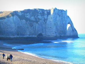 Étretat - Pebble beach with walkers, the Channel (sea) and the Aval cliff (chalk cliff) with its arc (the Aval gateway)