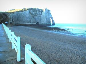 Étretat - Walkway of the seaside resort, pebble beach, the Aval cliff (chalk cliff) with its arc (the Aval gateway), and the Channel (sea)