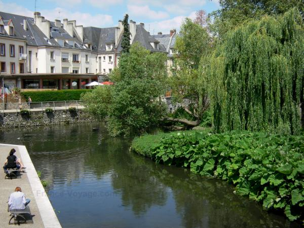Évreux - Walk along the banks of River Iton, trees along the water, and buildings of the town