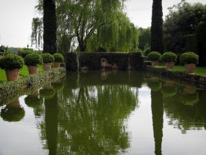 Eyrignac manor house gardens - Pond of water surrounded by shrubs in jars