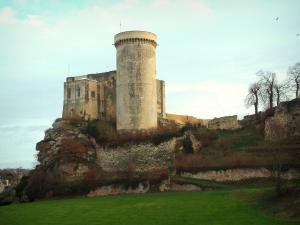 Falaise - William the Conqueror castle (Talbot tower, small keep and big keep) on a rocky mountain spur, trees and a cloudy sky
