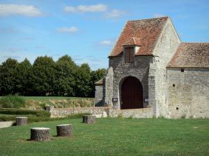 Fief des Epoisses stronghold - Entrance to the old medieval fortified farm, lawns and trees; in the town of Bombon