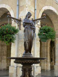 Fleurance - Fountain statue and covered market hall of the geranium-bedecked town hall; in thr Gers Lomagne