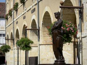 Fleurance - Fountain statue and covered market hall of the geranium-bedecked town hall