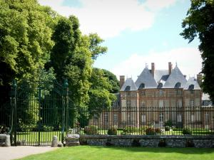 Fleury-la-Forêt - Château de Fleury-la-Forêt: facade of the château, trees in the park and entrance gate