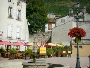 Foix - Pyrène square: fountain, lamppost with flowers, restaurant terrace and house facades in the old town