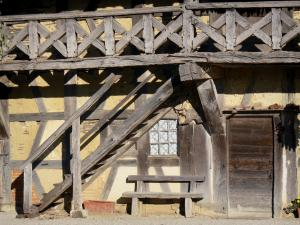 Forest farm-museum - Facade and balcony with wooden braces of the Bressan farmhouse; in Courtes, in Savoyard Bresse