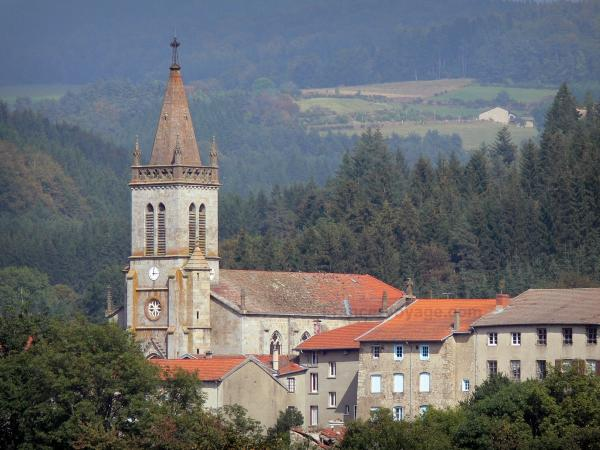 Forez mountains - Church bell tower and houses of the village of Saint-Anthème surrounded by pine trees and trees; in the Livradois-Forez Regional Nature Park