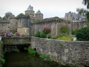 Fougères - Nançon river, flowers, shrubs, ramparts and towers of the medieval castle